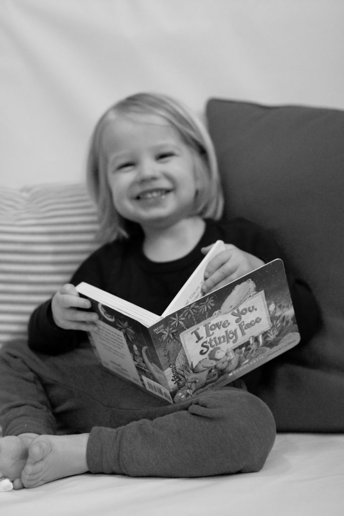 5 Favorite Valentine's Books for Tiny Book Lovers blog post | www.yourstrulyelizab.com | photo of boy smiling with book by Eliza B.